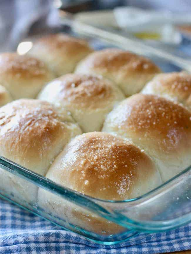 baked homemade rolls in a clear baking dish on top of a checkered napkin