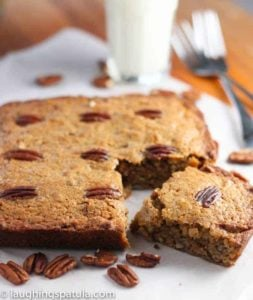 Pecan Snack Cake served up on parchment paper with glass of milk