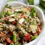 quinoa pilaf in white bowl with scallion garnish