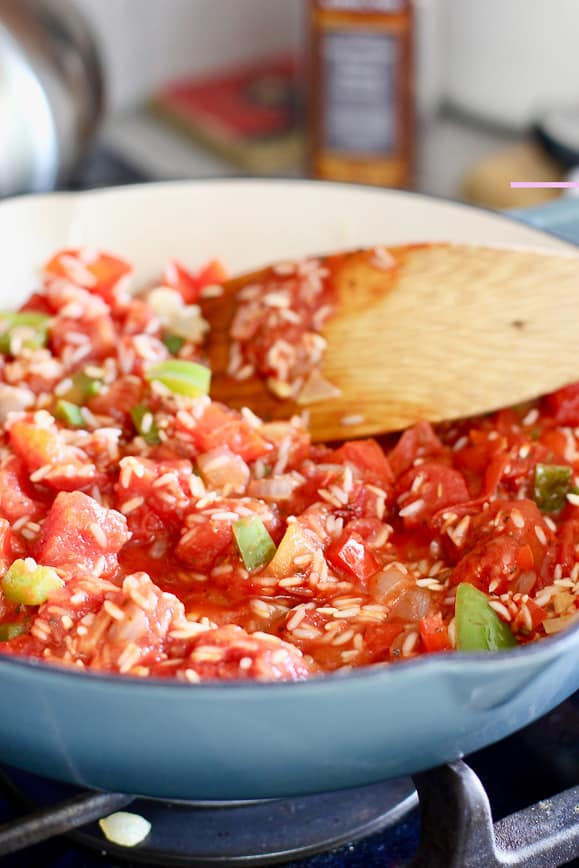 After tomatoes and broth are added to the rice, simmer, cover and cook