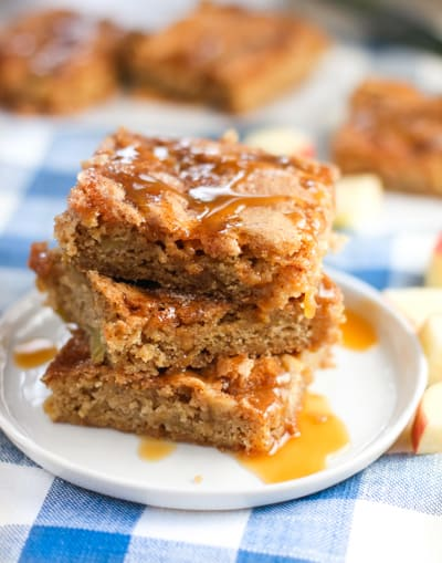 Apple bars stacked up on a white plate drizzled with honey