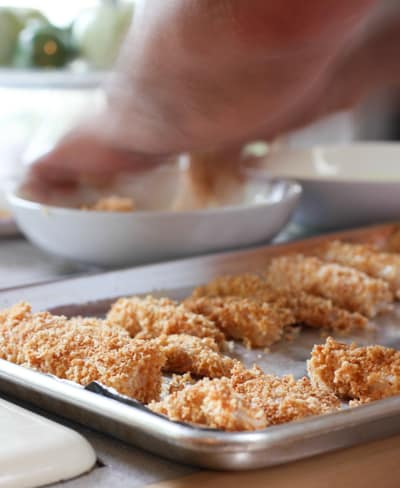 dipping fish into batter and coating with panko crumbs