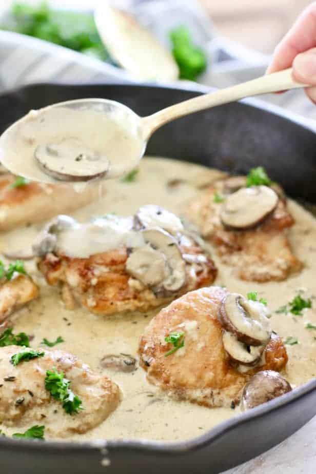 spooning mushroom gravy over chicken