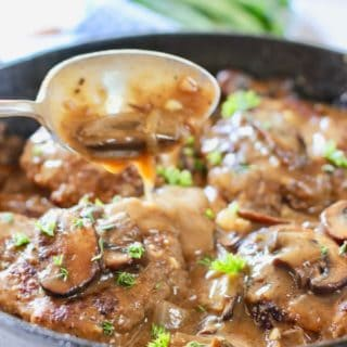 spooning gravy over Salisbury Steak