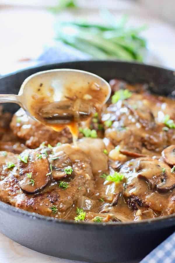 spooning gravy over Salisbury Steak