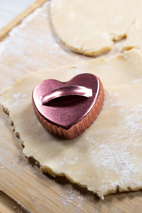 rolled out cream wafer dough on a bamboo cutting board with a copper heart cookie cutout on it