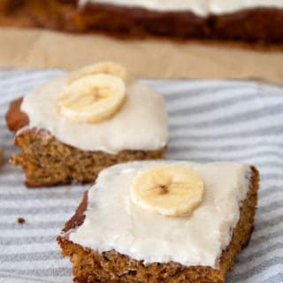 picture of banana bars on dish towel garnished with banana slices