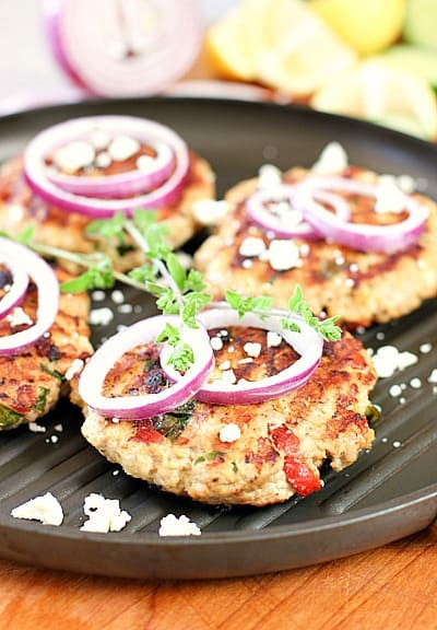 burgers on a grill pan with onion and spices