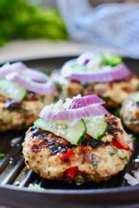 greek chicken burger with cucumber on a grill pan