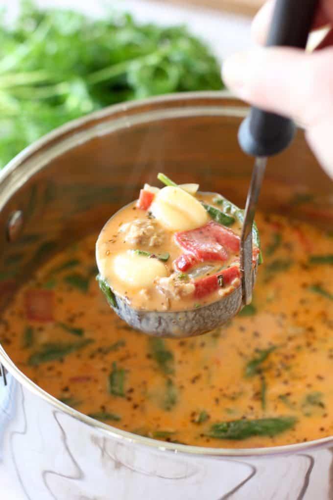 Gnocchi Sausage Soup in a ladle over a pot of soup