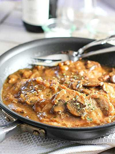 Skillet Pork Chops in Mushroom Gravy cooking in a skillet