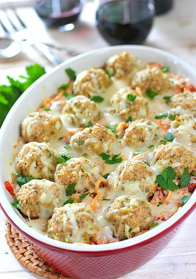 Meatballs and pasta in a casserole dish topped with melted parmesan, garnished with parsley.