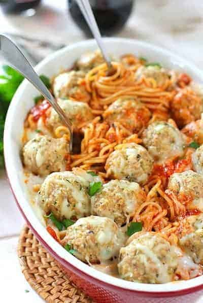 Meatballs and Spaghetti baked in a casserole dish, garnished with parsley and parmesan with forks spinning the pasta.