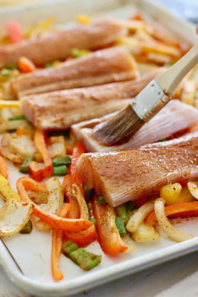 brushing seasoning on mahi fish fillet