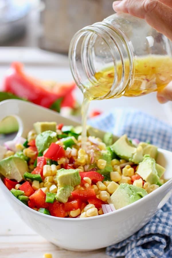honey lime vinaigrette poured onto fresh corn salad