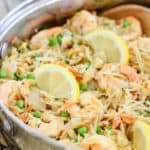 shrimp and orzo with sliced lemons in a skillet