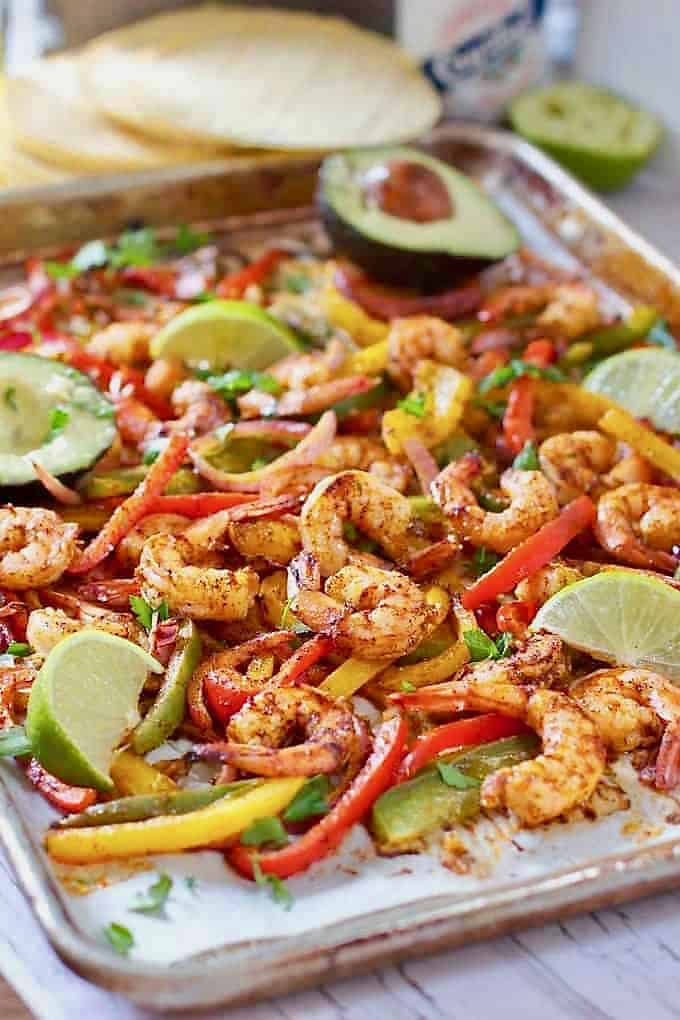 shrimp and sliced veggies on a tray for shrimp fajitas