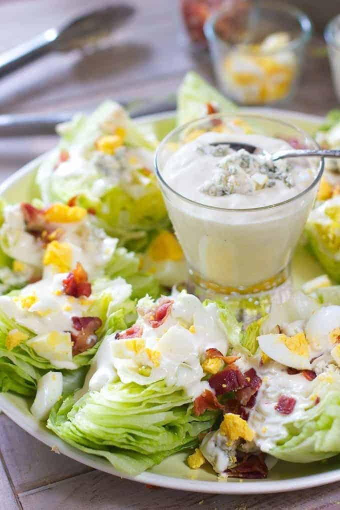 Wedge salad on a green platter with dressing