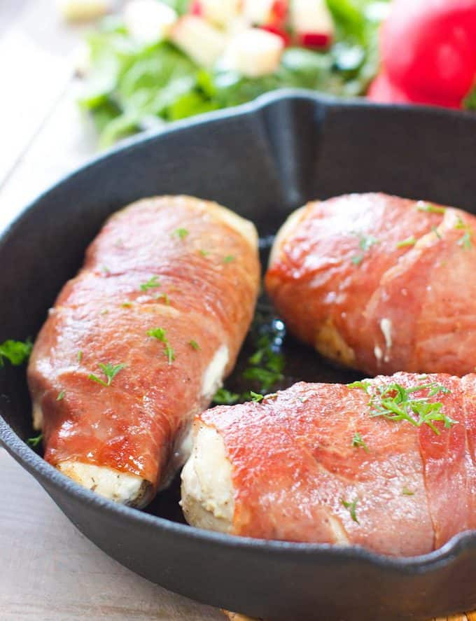 Seared chicken breasts wrapped in prosciutto in a cast iron skillet