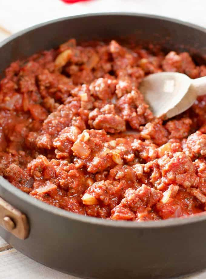 ground beef in a skillet with tomato sauce