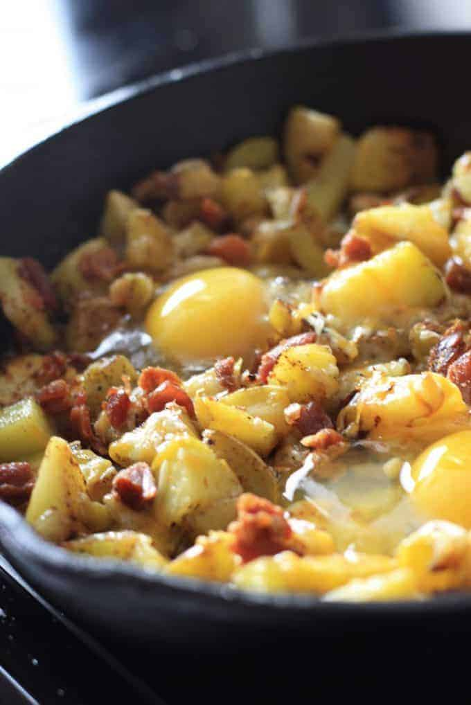 adding raw eggs to skillet to bake