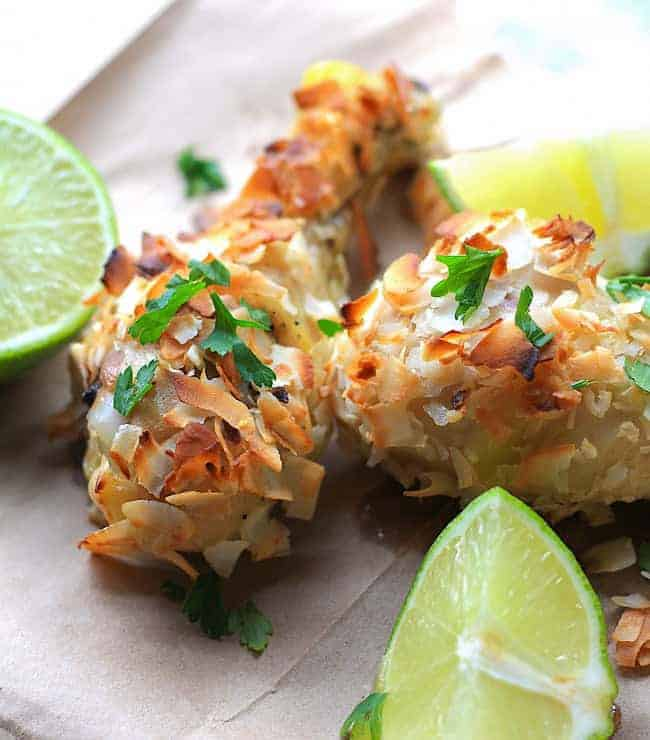Toasted shredded coconut smothered chicken drumsticks garnished with cilantro and lime wedges