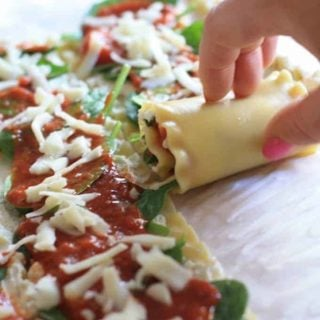 Lasagna roll ups on a parchment sheet filled with ricotta, spinach, marinara and grated parmesan cheese