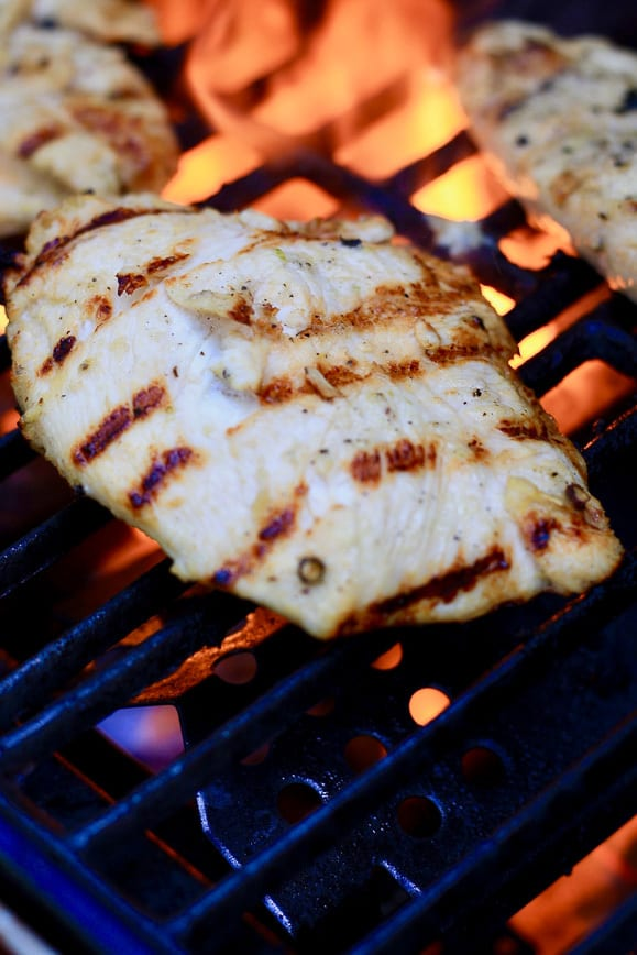 Lemon Grilled Chicken on the BBQ with grill marks and a flame in the background