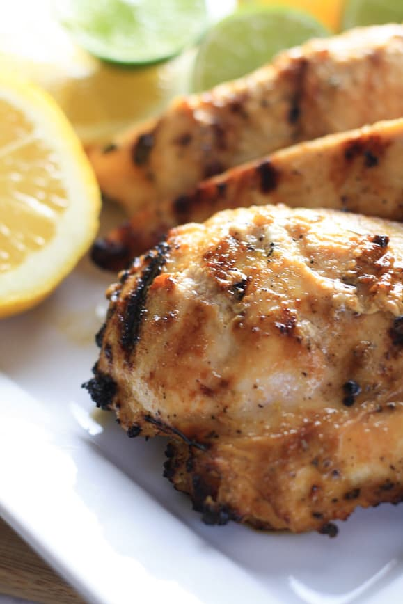 Lemon Grilled Chicken on a White Plate with Sliced Lemons and Limes in the Background