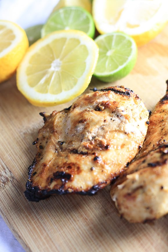 Lemon Grilled Chicken on a Cutting Board with Sliced Lemons and Limes