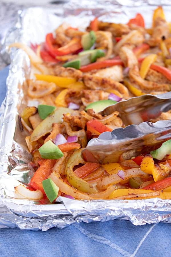 sheet pan fajitas tossed with tongs and garnished with avocado chunks