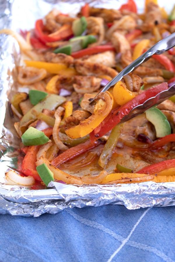 tongs grabbing fajitas on a sheet pan
