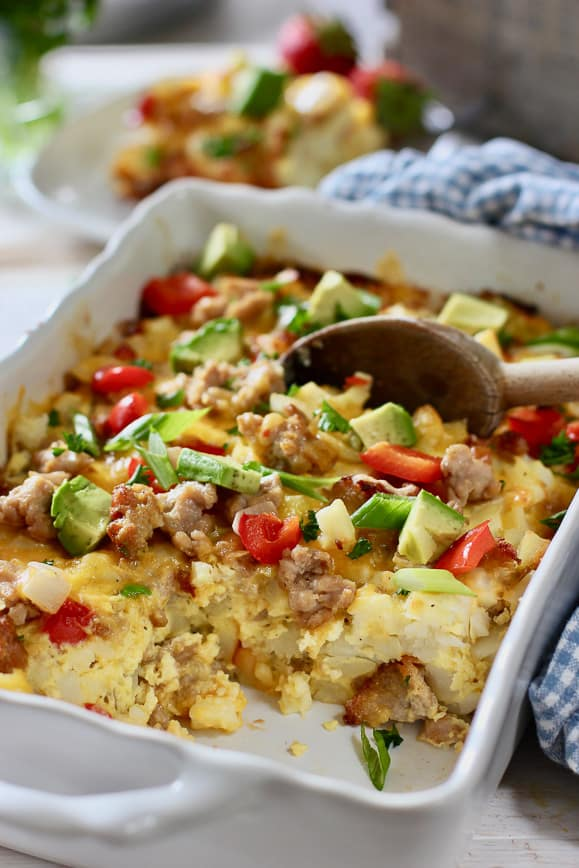 Baked Egg and Hash Brown Casserole being served with a wooden spoon