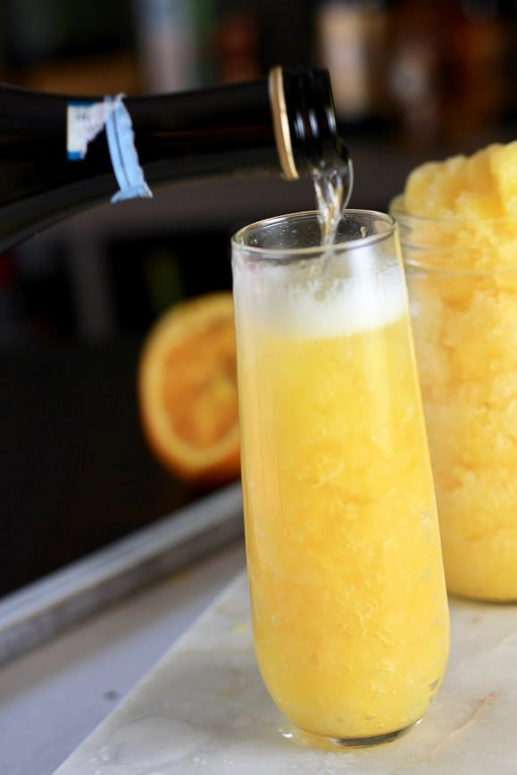 Prosecco being poured onto frozen orange juice mixture
