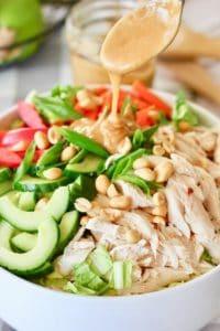 peanut dressing spooned onto thai peanut salad