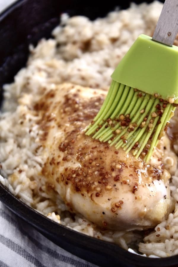 slathering honey mustard on chicken breast with pastry brush in pan of fluffy white rice