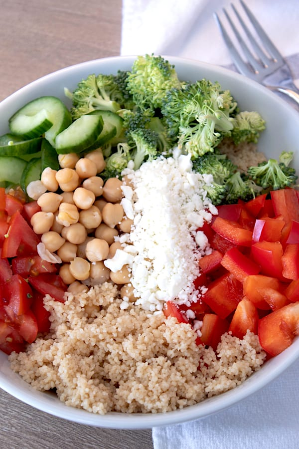 layered ingredients for couscous salad in a white porcelain bowl
