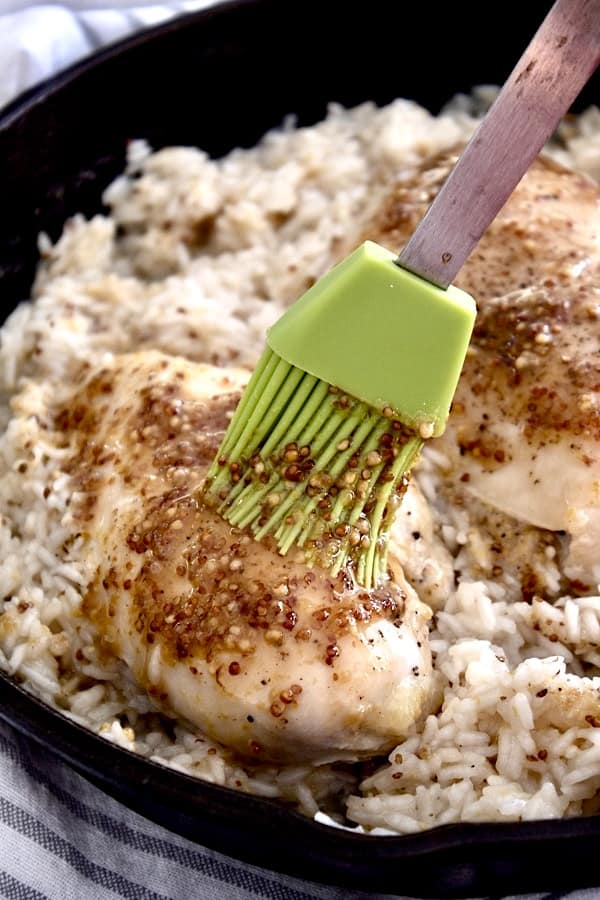 full view of honey mustard chicken slathered with honey mustard sauce in a black pan with fluffy rice