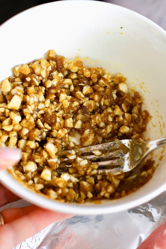 A white bowl filled with a mixture of brown sugar and garlic which resembled a paste