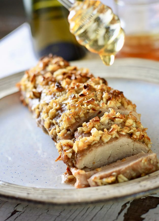 A pork loin on a white plate crusted with garlic and brown sugar with a glass drizzle stick drizzling honey
