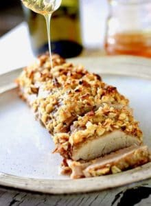 A pork loin on a tan ceramic plate crusted with garlic and brown sugar with honey drizzled over it