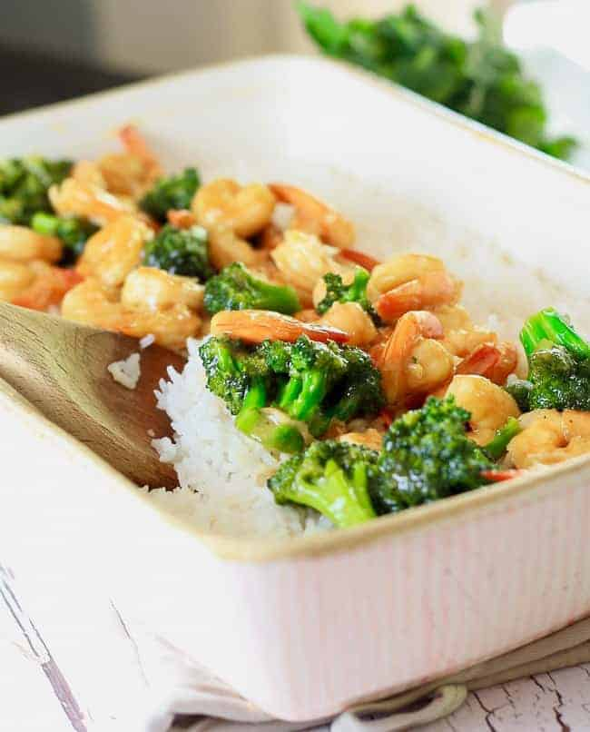 A light pink casserole dish filled with cooked white rice topped with shrimp and broccoli stir fry