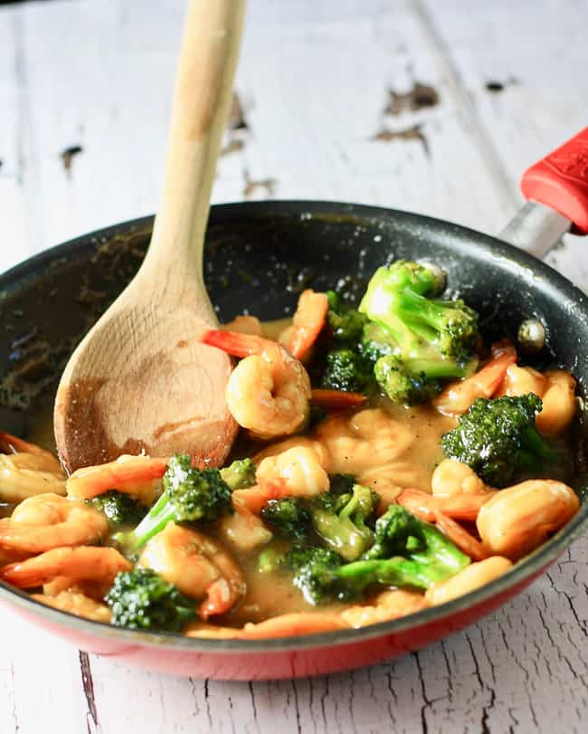 A shallow pan full of shrimp, broccoli and marinade with a wooden spoon