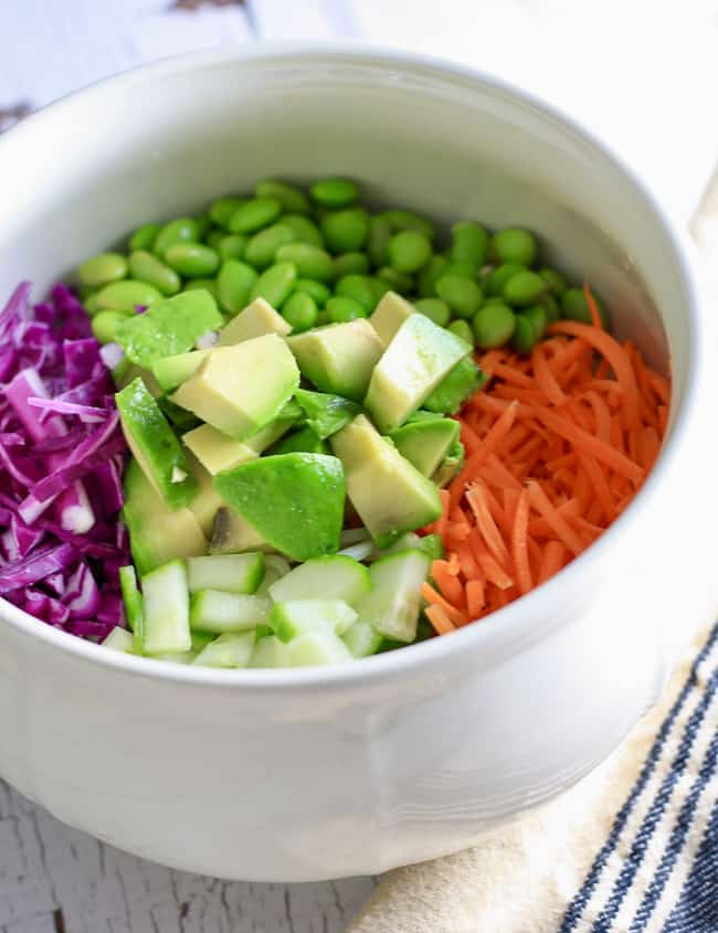 A white bowl filled with sliced veggies including avocado cucumber carrots and purple cabbage