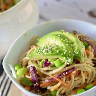 A white bowl filled with soba noodle salad and topped with avocado and sesame seeds