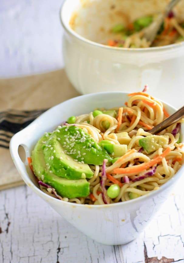 A white bowl filled with soba noodle salad toped with avocado and sesame seeds