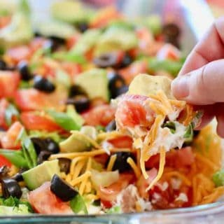 Skinny Taco Dip being scooped up with a tortilla chip