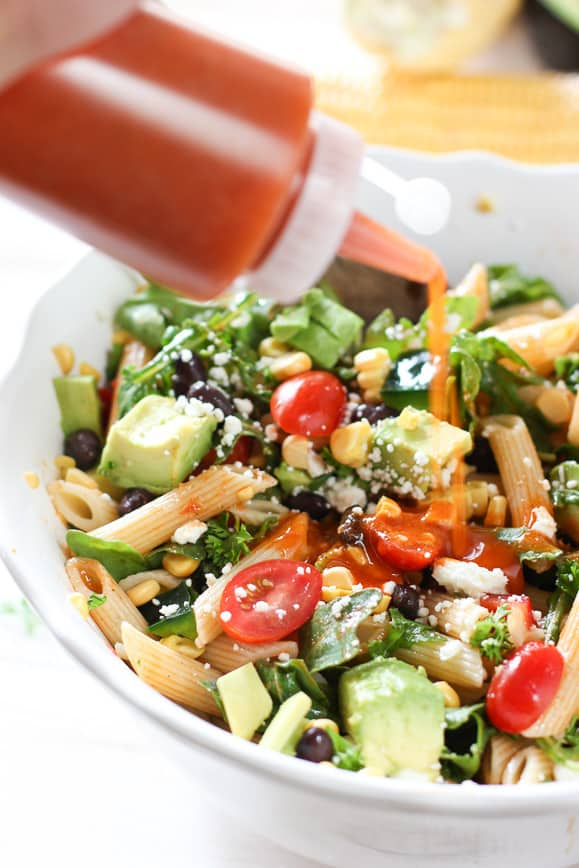 Adding dressing to Tex Mex Pasta Salad