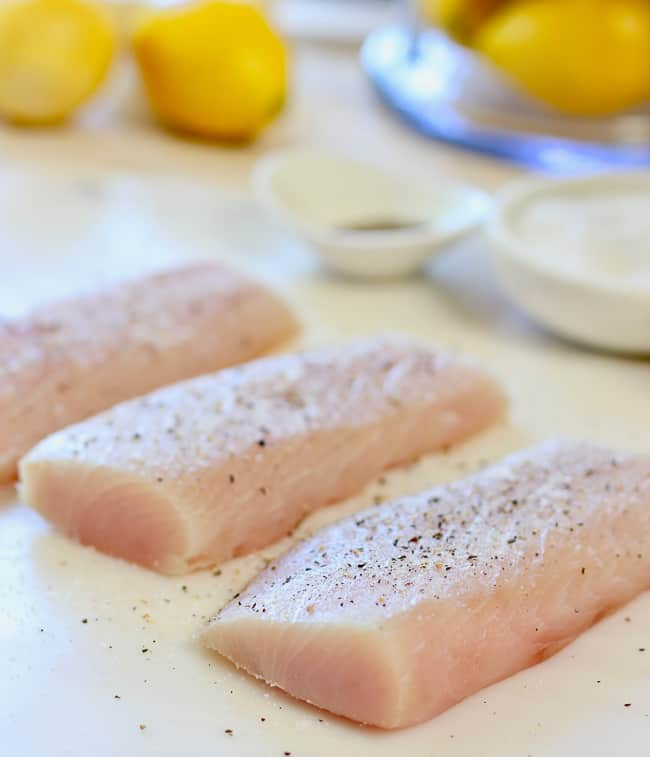 Fresh fish fillets being sprinkled with salt and pepper