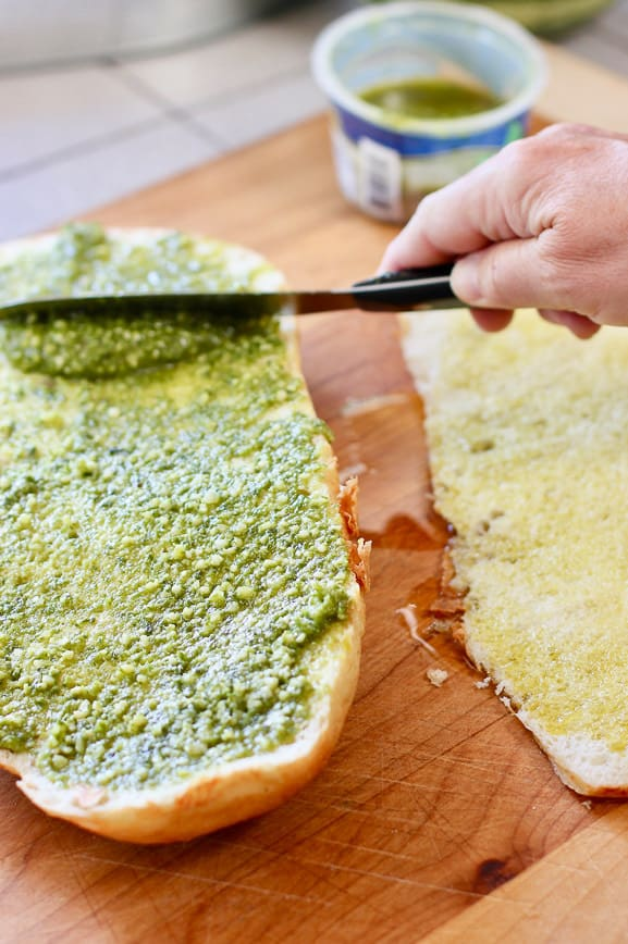 spreading pesto and olive oil on foccocia bread